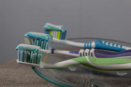Side view. On a transparent saucer lies a green toothbrush with toothpaste. Behind this brush lies two more brushes with paste.