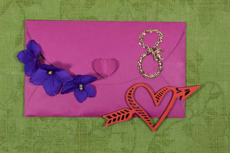 On a green background lies a pink envelope with three violets, a chain of 8 and a heart pierced by an arrow.
