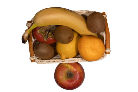 In the basket are ripe fruits lemon, mandarin, kiwi, banana and persimmon. Nearby lies an apple. Banco de Imagens