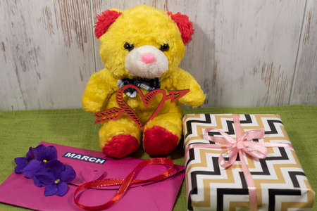 A toy bear sits on a table and holds a heart pierced by an arrow. Nearby lies an envelope with violets, number 8 and a gift box.