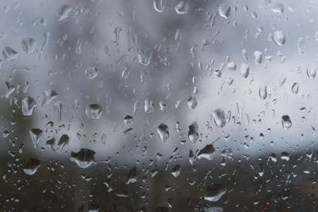 There are large raindrops on the window pane.