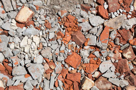 Background Texture Broken building materials - red bricks and cement chips - lie on the ground.
