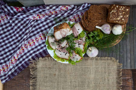 View from above. Against the background of a checkered napkin on the lettuce, there is bacon with pepper, dill and parsley. Nearby, on a round board, lies black bread, garlic and herbs.