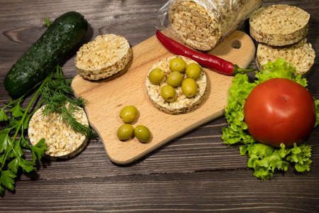 On a dark wooden background there is a cutting board, pieces of round whole grain bread, olives, lettuce, pepper, tomato, dill, parsley, cucumber. 免版税图像