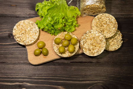 On a dark wooden background there is a cutting board, pieces of round whole grain bread, olives, lettuce.