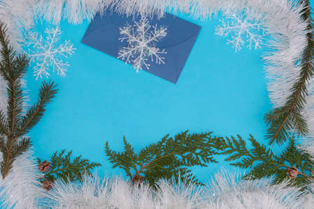 On a blue background, in a frame of white tinsel, there are branches of conifers, snowflakes, a blue envelope.