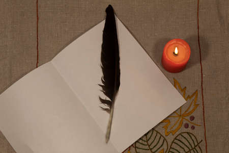 View from above. There is a red burning candle on an embroidered linen tablecloth, and a sheet of white paper on which lies a bird's feather.