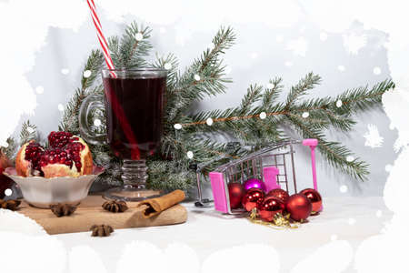 On a cutting board is a glass of pomegranate juice, a cinnamon stick and star anise, and a cut pomegranate. In the background there is a snow-covered spruce branch and an inverted cart with balls.