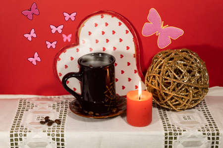 A white napkin with a cup of steaming coffee, candle and a decorative ball.