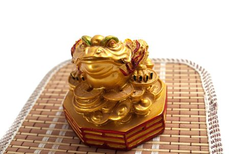 omens: Golden statuette depicting a toad sitting on a pile of coins symbolizes money and wealth, isolated