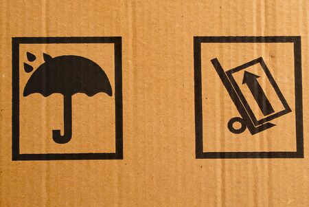 Fragment of a cardboard box with packaging warning signs. photo