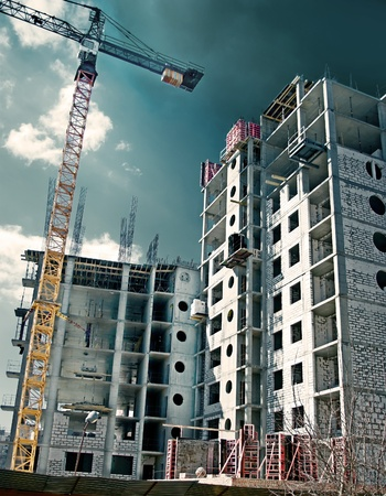 site: Construction site in the open air. Crane and unfinished buildings. Stock Photo