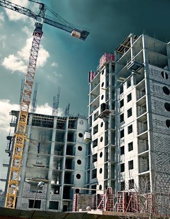 épület: Construction site in the open air. Crane and unfinished buildings. Stock fotó