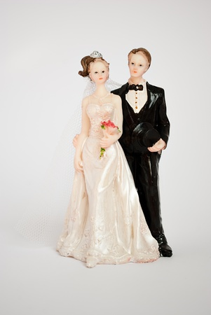 figurine: Figurine of bride and groom for the wedding cake on a gray background.
