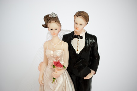 Figurine of bride and groom for the wedding cake on a gray background. photo