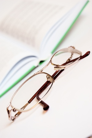 Reading glasses and a book on a white background. Toned. photo