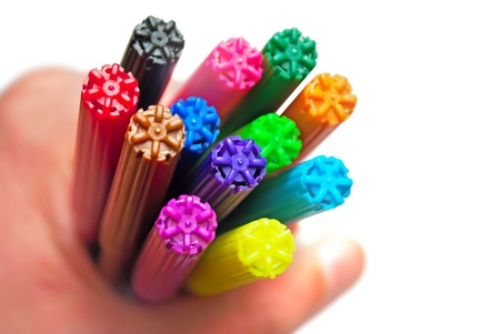 Colorful markers in hand, isolated on white. photo