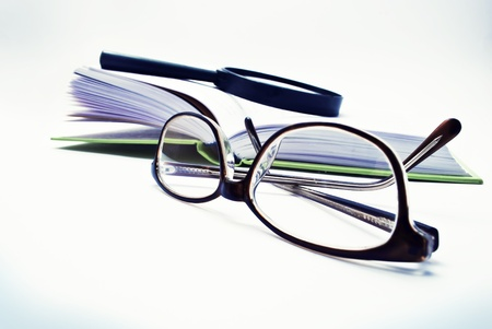 reading glasses: Set for reading - magnifying glass, glasses  and a book, toned. Stock Photo