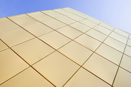 Facade wall of golden squares against the sky. Stock Photo - 9998841