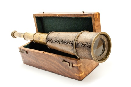 Antique spyglass and a wooden chest, isolated on white.