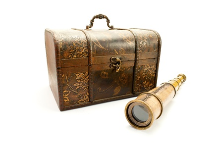 Antique spyglass and a wooden chest, isolated on white. photo