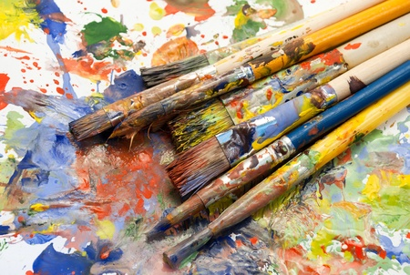 Different sizes paintbrushes against a background of multicolored paint spread. photo