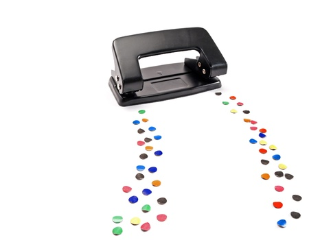 puncher: Hole puncher leaves a trail of colored circles, isolated on white. Stock Photo