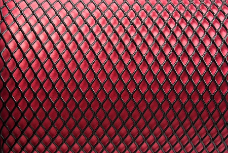Metal grid on a red background. Stock Photo - 10369419