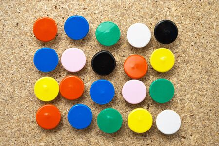 chipboard: Colorful thumbtacks in a wooden board.