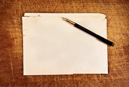 Ink pen and an old torn envelope on a wooden background. Stock Photo
