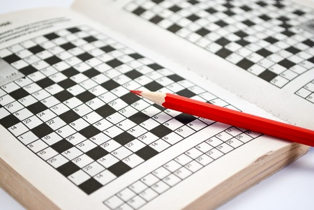 The book of crossword puzzles and red pencil. Foto de archivo
