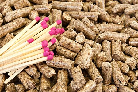 Solid background of yellow wooden pellets and some pink-head matches. photo