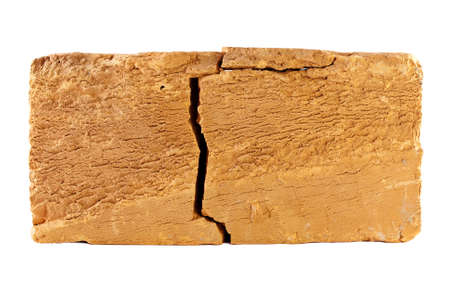 The simple brick with a large crack, isolated on white. photo