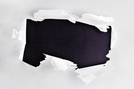 cut through: Breakthrough paper hole with black textured background.