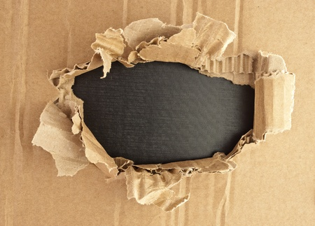 Breakthrough cardboard hole with black textured background. Stock Photo - 11277446