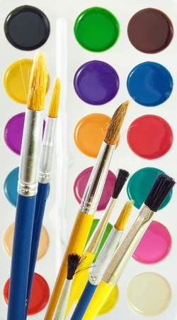 Several paintbrushes against the set of watercolor paints. photo