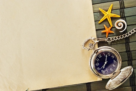 Marine themed frame of paper sheet, watches and seashells on a wooden mat. photo