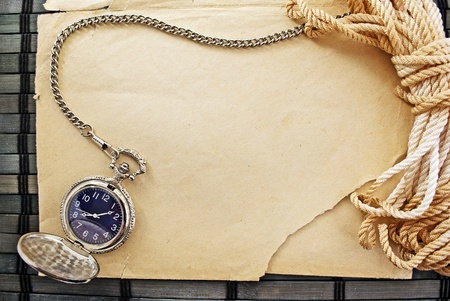 Marine themed frame of paper sheet, watches and sailor rope on a wooden mat. photo