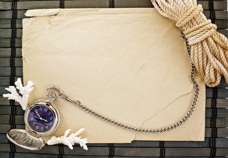 Marine theme frame of paper sheet, watches and sailor rope on a wooden mat. photo