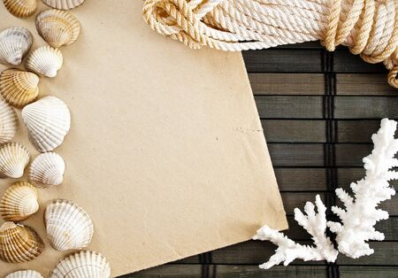 Marine themed frame of paper sheet, sailor rope, coral and seashells on a wooden mat. photo