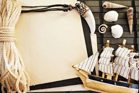 Marine themed frame of paper sheet, sailor rope, little ship and seashells. Stock Photo
