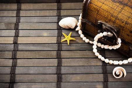 Little chest with treasures and few seashells on a wooden mat.