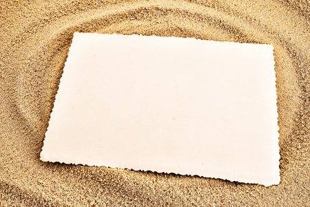 White empty card on a sand. Summer background theme. photo
