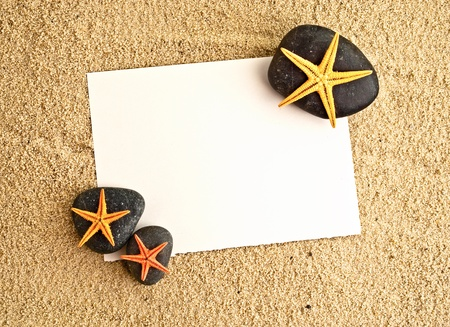 Empty paper sheet on a sand with small detail of sea-stars on a stone. photo