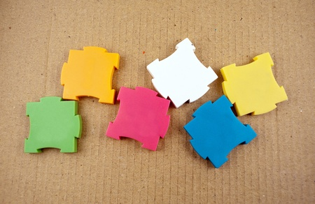 Few colorful empty puzzles on a cardboard background. Stock Photo - 12957300