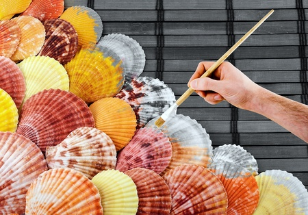 colorize: Painters hand with paintbrush colorize lots of seashells.