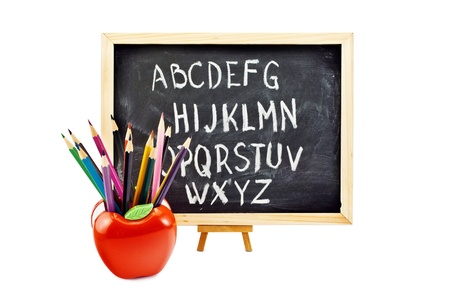 Preschool still life of a blackboard and some colorful pencils in apple-shaped stand, isolated on white. photo