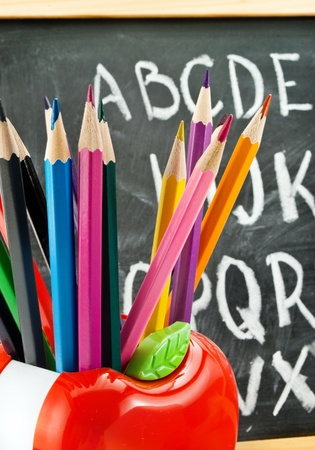 Closeup of colorful pencils against school blackboard. photo
