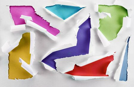 to break through: Some torn holes on a paper sheet with colorful backgrounds.