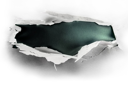 Breakthrough paper hole with dark background. Stock Photo